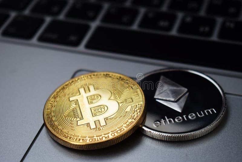 Monete di Ethereum e di Bitcoin su un computer portatile fotografia stock libera da diritti