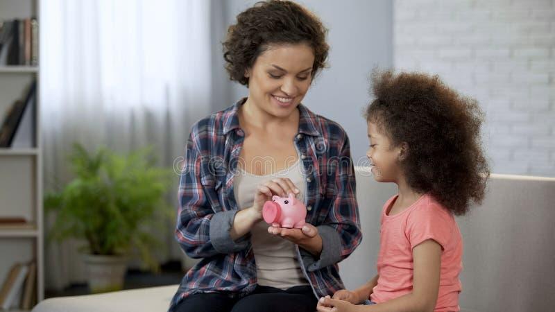 Monete di lancio della figlia e della mamma nel porcellino salvadanaio, soldi di risparmio per i presente fotografia stock libera da diritti