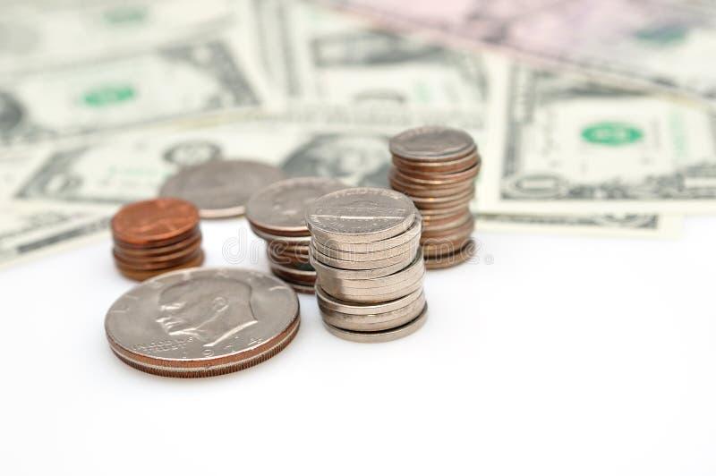 Monete e banconote del dollaro isolate su fondo bianco. fotografia stock libera da diritti