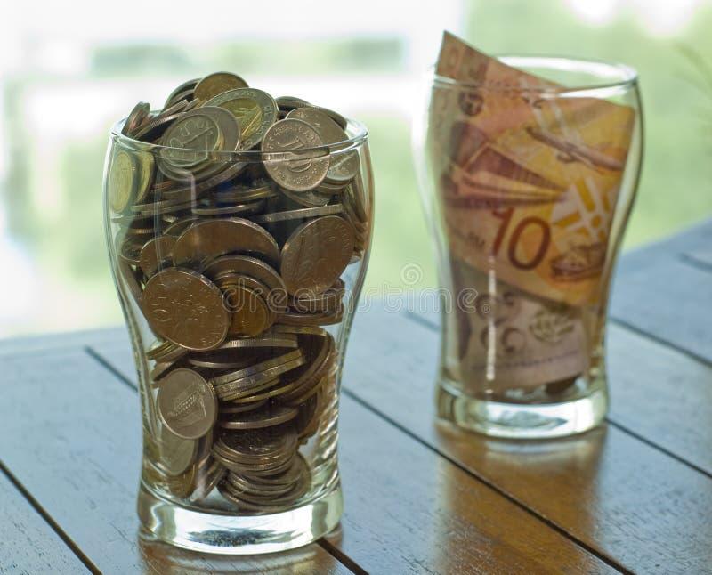 Monete e bevanda della nota per carità fotografie stock