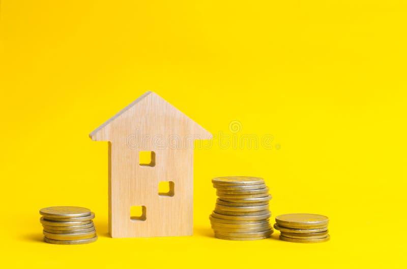 Monete e casa di legno su un fondo giallo Concetto del bene immobile Comprando, vendendo ed affittando una casa Prestito per un a fotografia stock
