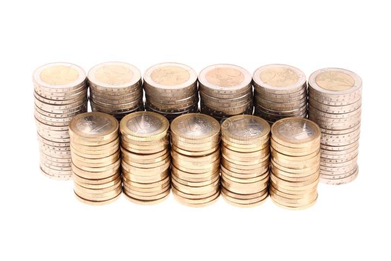 Monete organizzate in colonne e righe isolate immagine stock