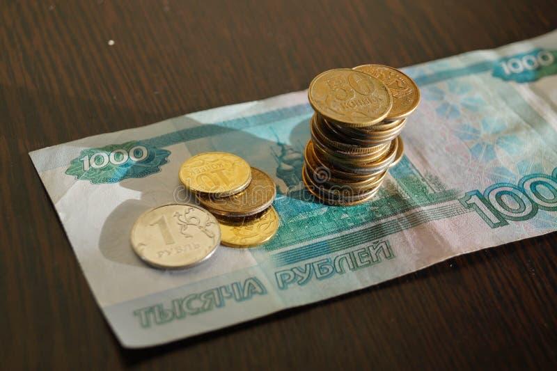 Monete russe su una banconota in 1000 rubli immagini stock libere da diritti