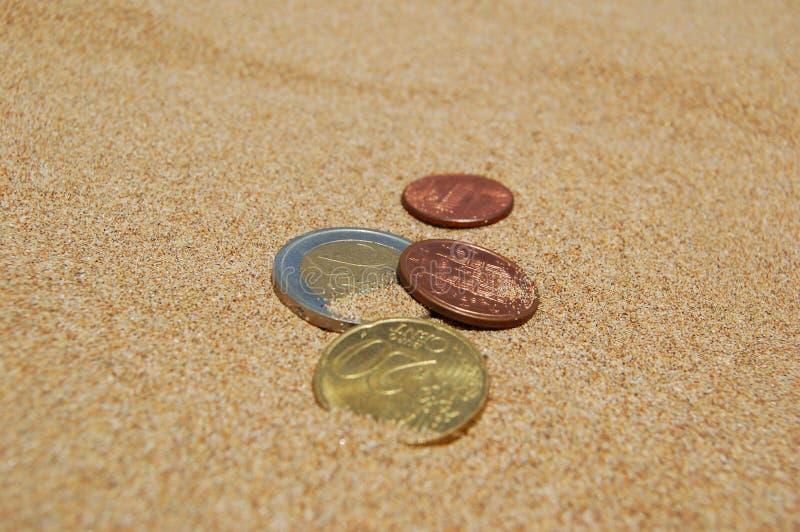 Monete in sabbia fotografia stock