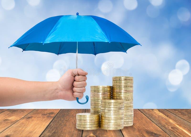 Monete sotto un ombrello blu fotografia stock