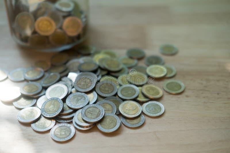 Monete tailandesi all'interno e all'esterno del barattolo di vetro, valuta di baht tailandese fotografie stock libere da diritti