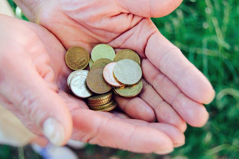 Monete in vecchie mani della nonna fotografie stock libere da diritti