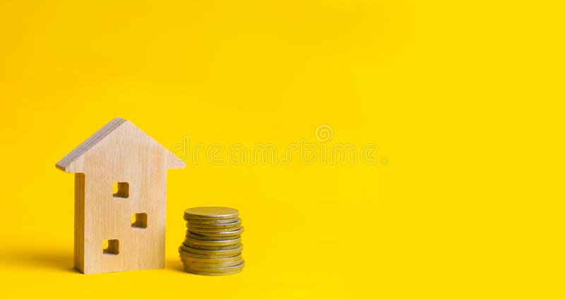 Monety i drewniany dom na żółtym tle koncepcja real nieruchomości Kupienie, sprzedawanie i wynajmowanie, dom Pożyczka dla mieszka zdjęcia royalty free