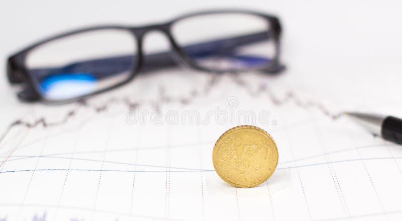 Monety, kalkulator i szkła na wzrostowym pieniężnym wykresie, obrazy royalty free