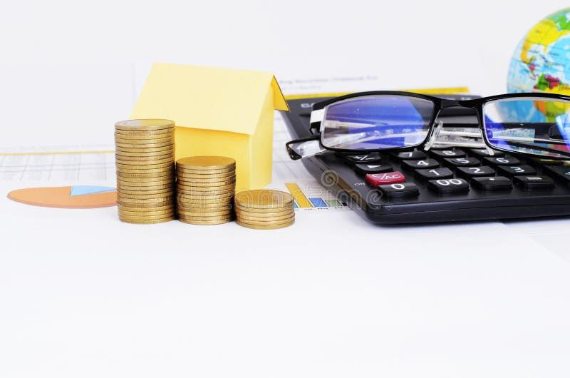 Monety, koloru żółtego papieru dom, Eyeglasses i kalkulator na biznesowej mapy dokumencie brogują zdjęcia stock