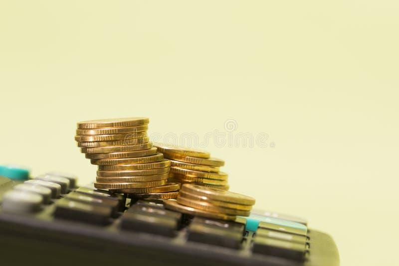 Monety umieszczone na kalkulatorach, statystykach gospodarki finansowej i obliczania bogactwa obrazy stock