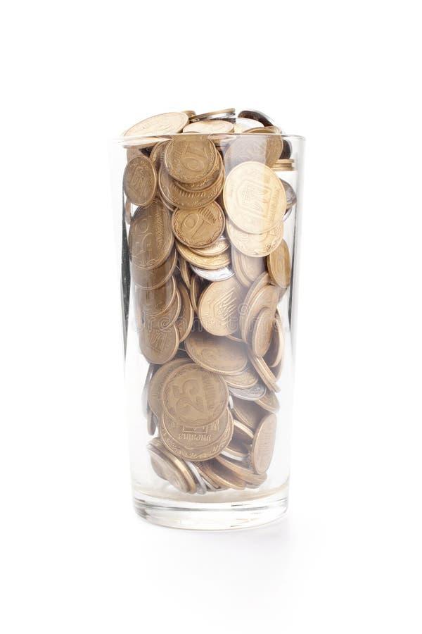 Monety w szklanej filiżance na bielu fotografia royalty free