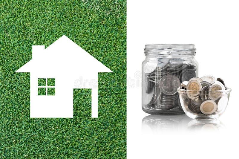 Monety w szklanym słoju kupować nowego dom - oszczędzanie pieniądze dla przyszłościowego pojęcia obraz royalty free