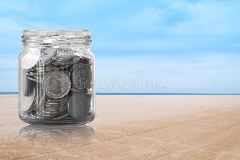 Monety w szklanym słoju na plażowym natury tle obraz royalty free