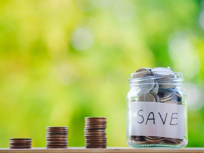 Monety w szklanym słoju na plamy tle Pieniądze ratuje pieniężnego pojęcie obrazy stock