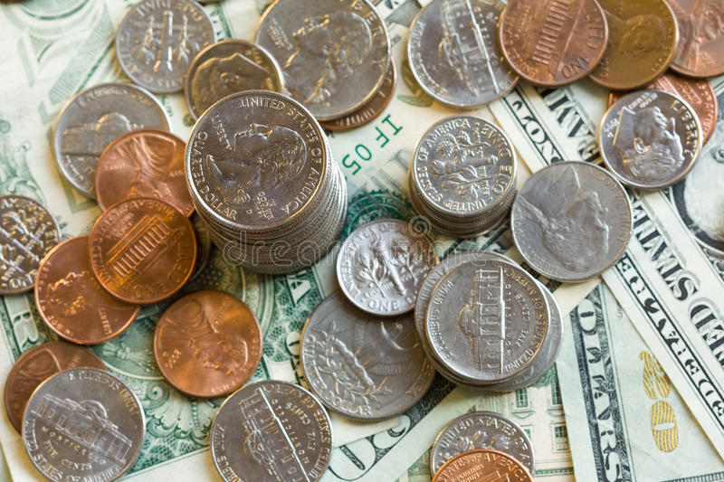 Money. Detail of US dollars and coins with focus on quarter coin stock image