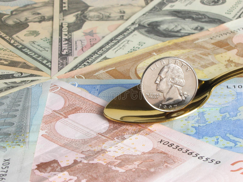 Money. Quarter dollar in gold spoon on a background of dollars and euro royalty free stock photos