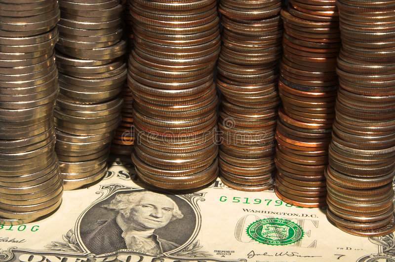 Money. Assorted coins on a one dollar bill stock photography