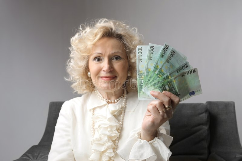 Money. A smiling senior woman with money in her hand stock photography