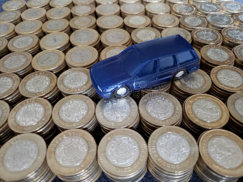 The money in the automotive industry, figure of a blue car and coins of ten mexican pesos. Trading and exchange, bank and commerce, price of buy and sell, cash royalty free stock photo