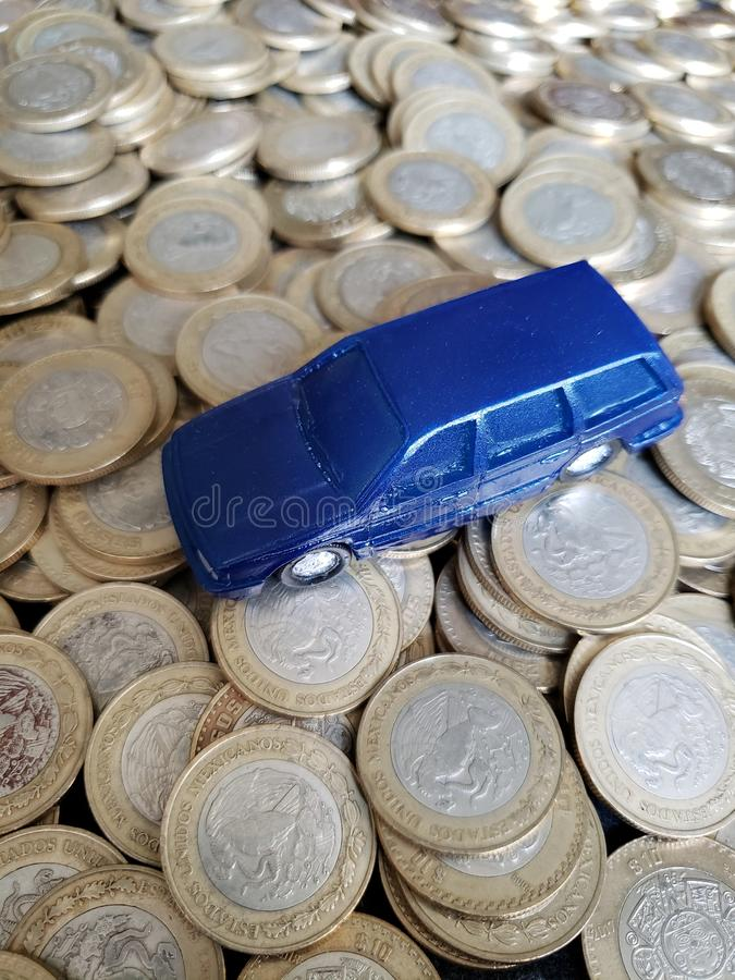 The money in the automotive industry, figure of a blue car and coins of ten mexican pesos. Trading and exchange, bank and commerce, price of buy and sell, cash stock photography
