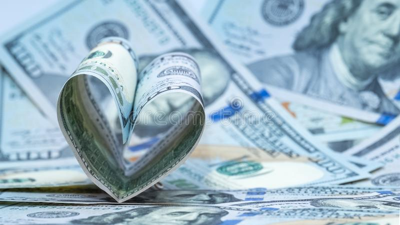 One hundred dollars US banknote in the shape of a heart. Money background. Concept financial love and a gift for Valentine`s Day. Money background. One hundred royalty free stock photography