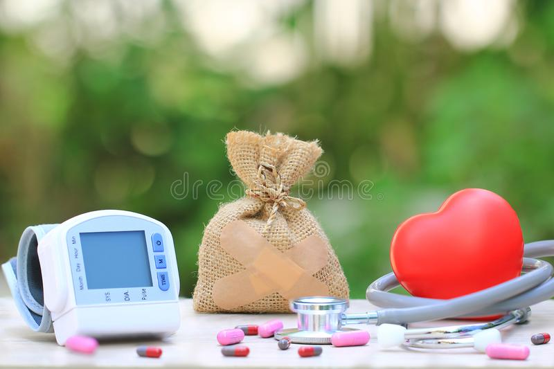 Money bag attached to the plaster with Medical tonometer for measuring blood pressure with stethoscope and red heart on natural g stock photography