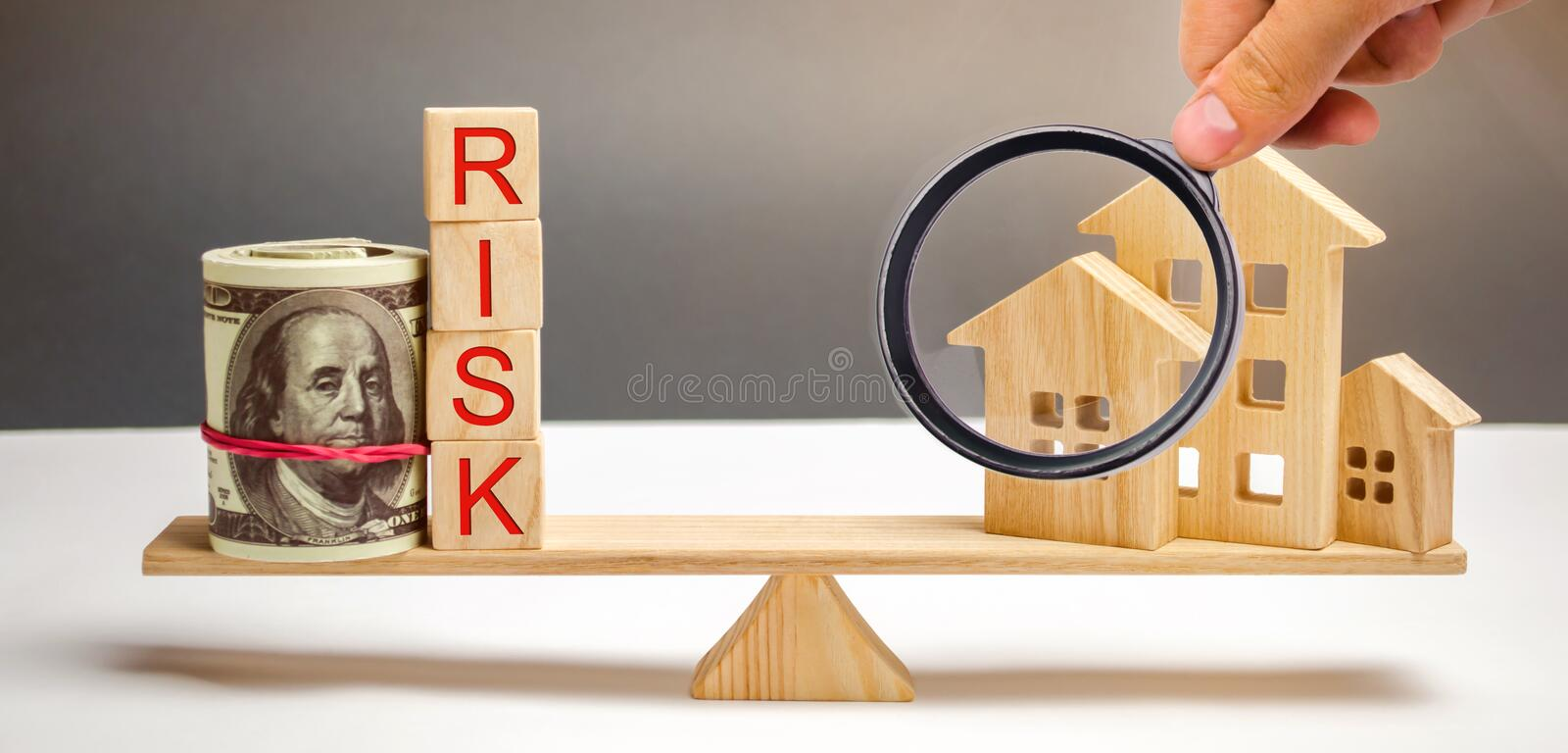 Money bag, blocks with the word Risk and a wooden house on the scales. The concept of losing money when investing in real estate. Risks of losing a home or stock photos