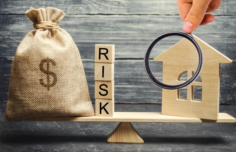 Money bag, blocks with the word Risk and a wooden house on the scales. The concept of losing money when investing in real estate. Risks of losing a home or stock photo