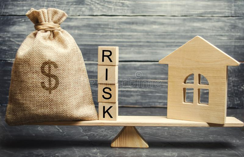 Money bag, blocks with the word Risk and a wooden house on the scales. The concept of losing money when investing in real estate. Risks of losing a home or stock image