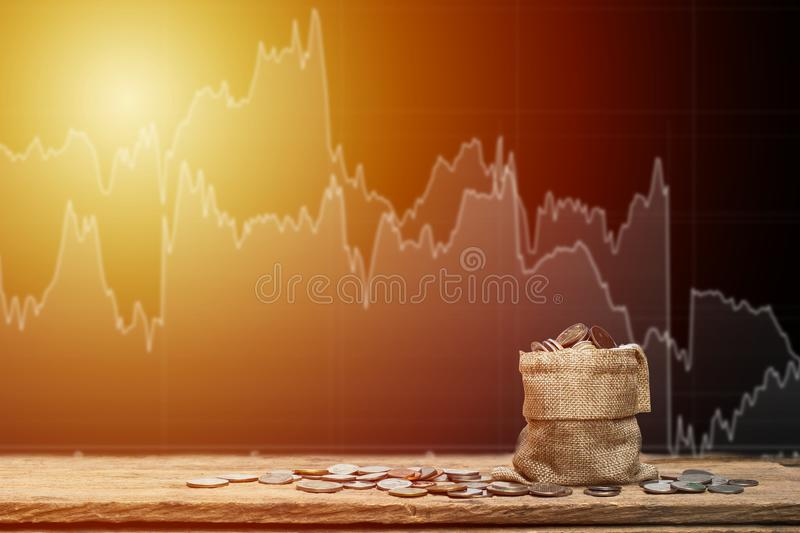 Money bag and money coins on wood table with stock graph as back royalty free stock images