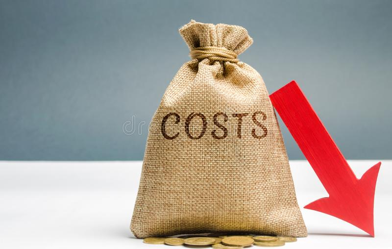 Money bag with coins with the word Costs and a down arrow. Reduction. Expenses cut. The concept of business and finance. Money royalty free stock photography