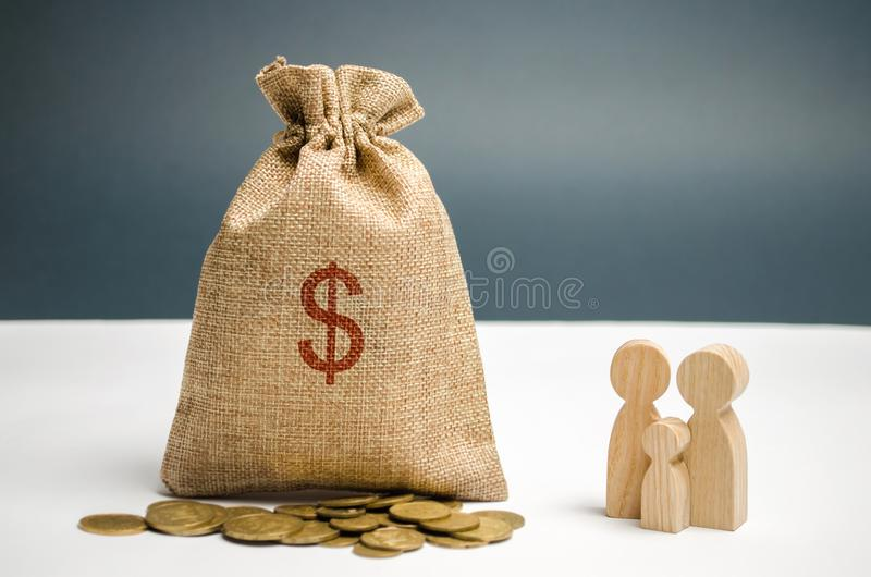 A money bag with a dollar sign is standing near the family. The concept of management a family budget. Profit and income. Savings. And accumulation of money royalty free stock photo