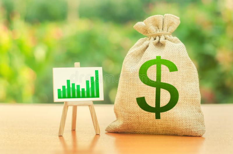 Money bag with dollar symbol and a stand with a green growth trend chart. Increase profits and wealth. growth of wages. Favorable stock photography
