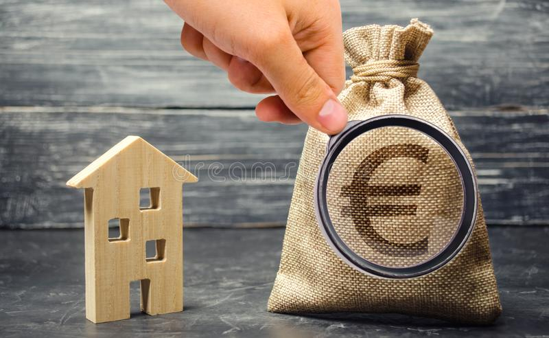 Money bag with euro sign and wooden house. The concept of real estate investing. The accumulation of money to buy a home. Rent. Apartment. Payment of mortgage royalty free stock photography