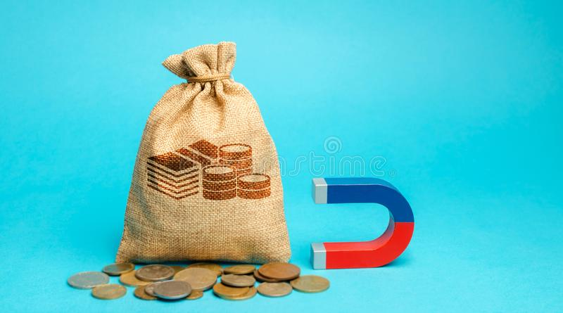 Money bag and magnet. Attracting investments for business purposes and startups. Increase profits and attract new customers. Salary, bonus, cashback. Strategy royalty free stock photography