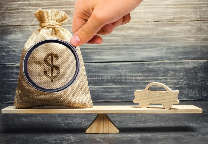 A money bag with a miniature wooden car on the scales. Auto insurance. Accumulation of money to buy a car. Saving money for a. Dream. Purchase the auto royalty free stock photography