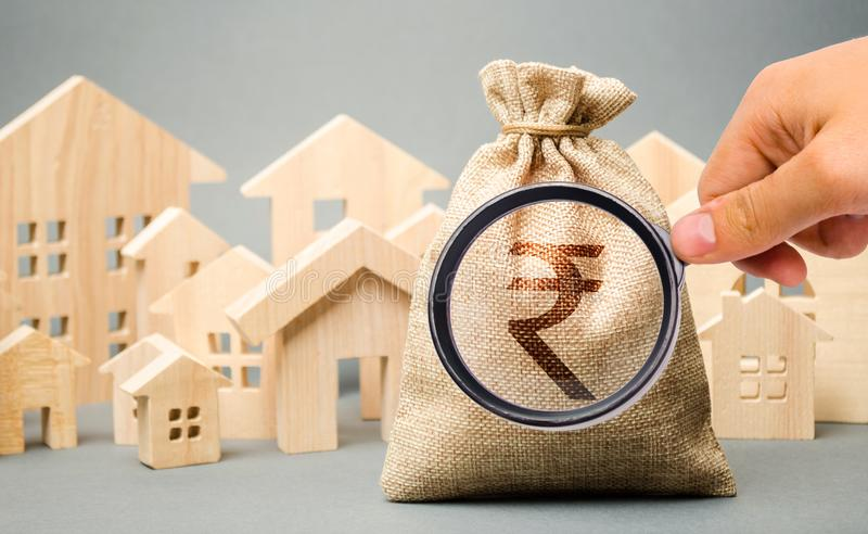 Money bag with a sign indian rupee rupiah and wooden houses. The concept of real estate market. Pricing and demand. City budget. Rental and sale of housing royalty free stock photo
