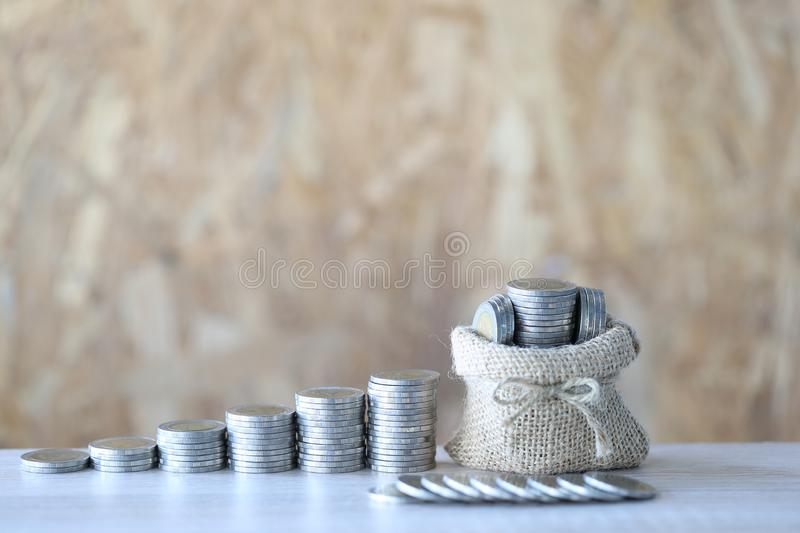 Money bag with stack of coins money on wooder background, Saving for prepare in future and Business investment concept.  stock photography