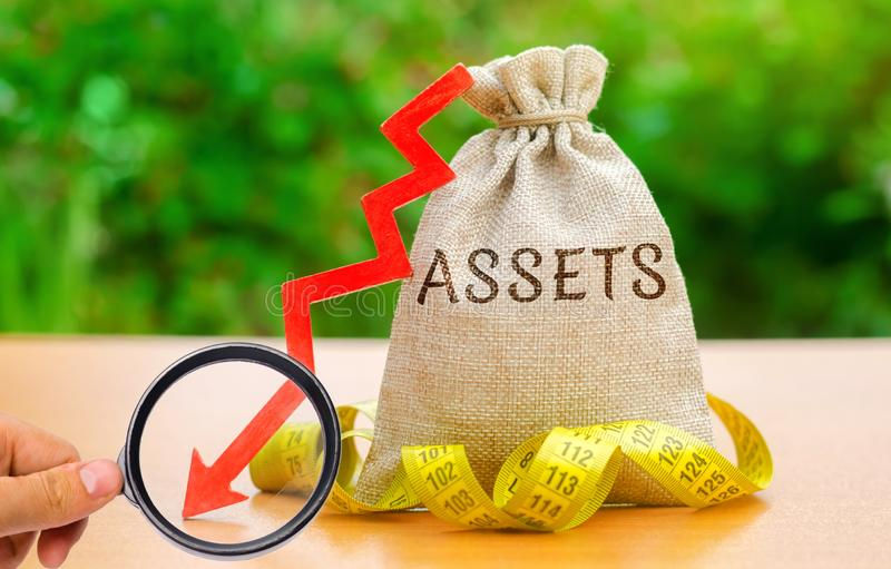 Money bag with tape measure and the word Assets with down arrow. Falling asset, liquidity and value. Analysis of the return on. Asset. Capital outflow. Bad royalty free stock images