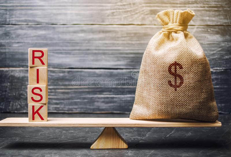Money bag and wooden blocks with the word Risk. The concept of financial risk. Justified risks. Investing in a business project. royalty free stock image