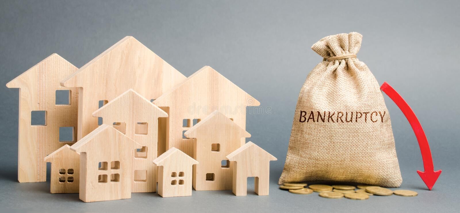 A money bag with the word Bankruptcy, a down arrow and wooden houses. Bankruptcy auction. Mortgaged property. Financial collapse. The decline in the real stock image