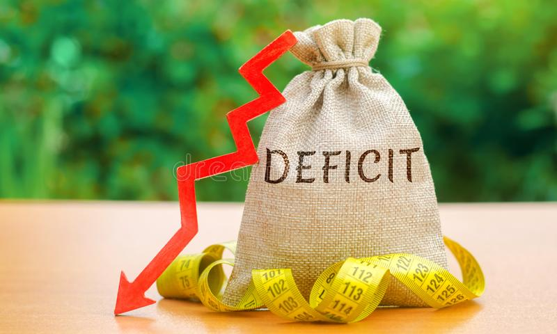 Money bag with the word Deficit and tape measure with down arrow. Budget deficit concept. Low profit. Financial costs. Bankruptcy. Adverse conditions in royalty free stock photos