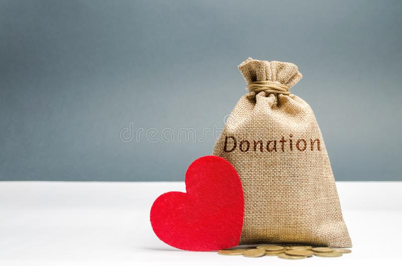A money bag with the word Donation and a red heart. Accumulation of money for a medical donation. Health care. Saving. Social royalty free stock photo