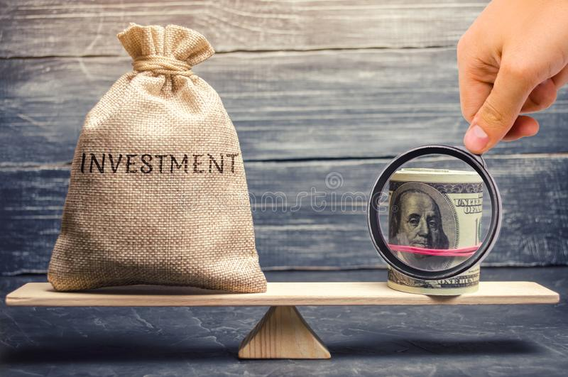 Money bag with the word Investments and dollars on scales. Attraction of financial resources for investment projects. Risk. Assessment and profit forecast royalty free stock images