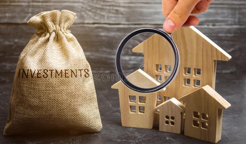 Money bag with the word Investments and wooden houses. The concept of attracting investment in real estate. Search for investors. For construction. Investment royalty free stock images