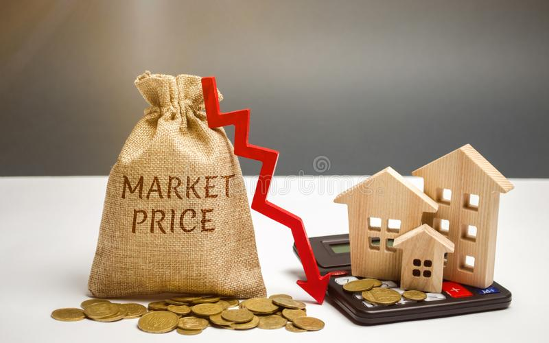 Money bag with the word Market price and an arrow down with a calculator and wooden houses. Reduced housing prices. The fall and royalty free stock photos
