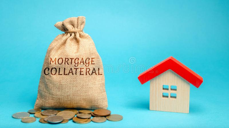 Money bag with the word Mortgage collateral and wooden house. Affordable housing programs for young families. Governmental support stock photo