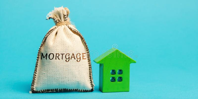 Money bag with the word Mortgage and wooden house. The accumulation of money to pay interest rates on mortgages. Buying a property royalty free stock photography