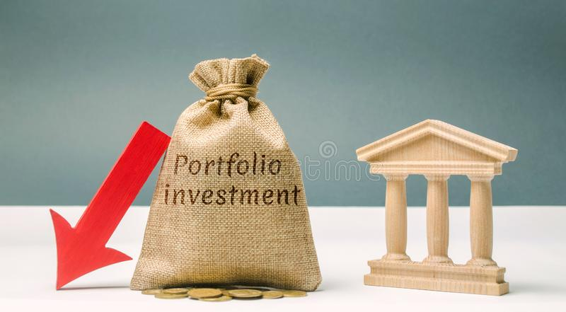 Money bag with the word Portfolio Investment and a down arrow near the bank. The outflow of deposits. The fall of the bank`s. Solvency. Bankruptcy. Loss of royalty free stock photo